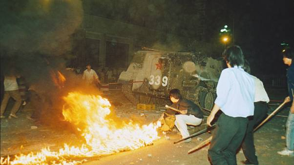 Student protesters put a barricade in front of a burning armored personnel carrier that rammed through student lines, June 4, 1989.