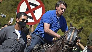 Brazil's President Jair Bolsonaro rides a horse greeting supporters outside the presidential palace in Brasilia, Brazil, Sunday, May 31, 2020. (AP Photo/Andre Borges)