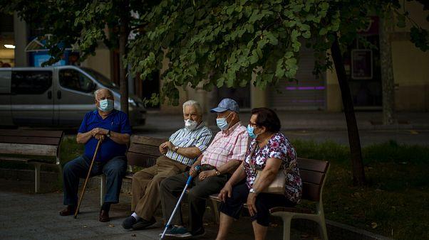 Un grupo de ancianos sentados con mascarillas en Barcelona, España