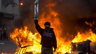 A protester holds a skateboard in front of a fire in Los Angeles