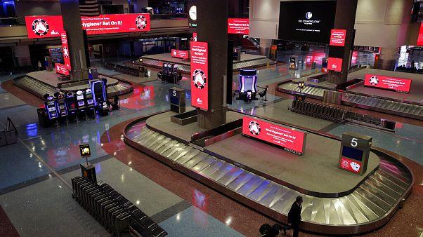 Ein Mann geht durch die Gepäckausgabe am Flughafen in Las Vegas, Freitag, 29. Mai 2020. Rot leuchten Schilder mit Hinweisen gegen Coronavirus-Infektionen.