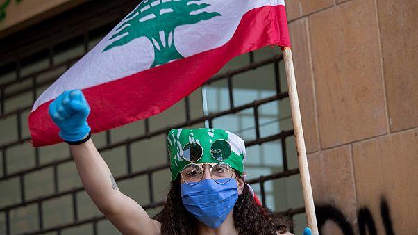 متظاهرة لبنانية ترتدي كمامة واقية كإجراء وقائي لمكافحة عدوى فيروس كورونا
