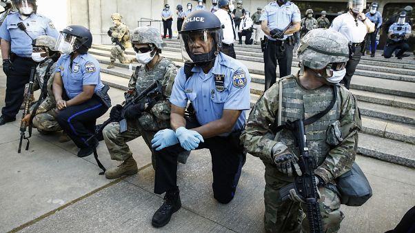 Polícias ajoelhados em sinal de solidariedade
