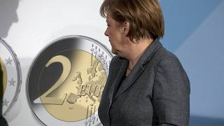 German Chancellor Angela Merkel turns to a panel showing a two Euro coin during the presentation of a special edition of the coin at the chancellery in Berlin, Germany, Thursd