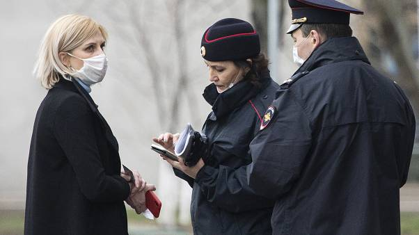 In this April 8, 2020, file photo, police officers check documents of a woman to ensure she is complying with a self-isolation regime due to coronavirus in Moscow, Russia