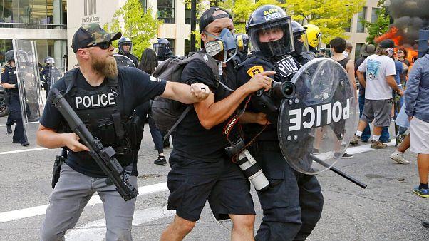Agentes de policía empujan a un fotógrafo el sábado en Salt Lake City