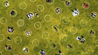 أشخاص يحافظون على مسافات التباعد الاجتماعي في إحدى الحدائق