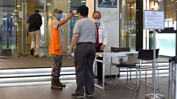 التثبت من درجة حرارة رجل عند دخوله مبنى في سنغافورة - 2020/06/02