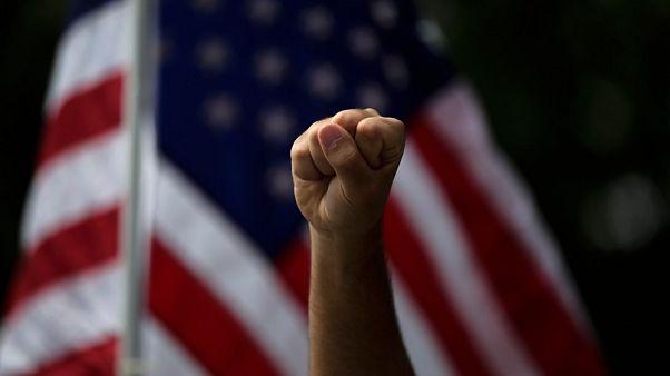 Un manifestante alza il pugno, durante una protesta ad Anaheim, in California