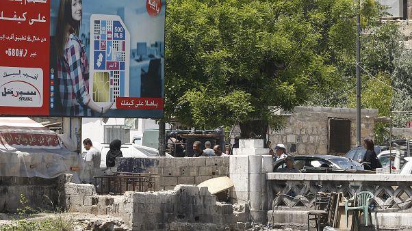 أناس يمشون في دمشق قرب لوحة إشهارية لأكبر مشغل للهواتف المحمولة في البلاد يملكها رامي مخلوف - 2020/05/11