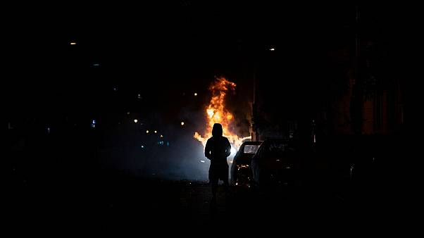 A demonstrator watches a car burn during protests over the death of George Floyd, near the White House in Washington, D.C.