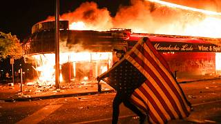 A protester carries a U.S. flag upside, a sign of distress, next to a burning building, early Friday, May 29, 2020, in Minneapolis.