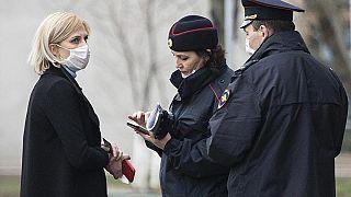 عناصر من لشرطة الروسية يتحققون من وثائق امرأة للتأكد من أنها تلتزم بنظام الحجر الصحي أبريل2020