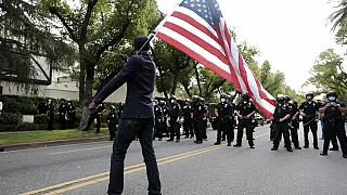 Un manifestante ondea una bandera ante policías en Los Ángeles
