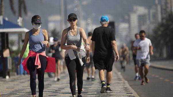 Brezilya'nın Rio de Janeiro kentindeki Ipanema plajında deniz kıyısında yürüyüş yapan vatandaşlar
