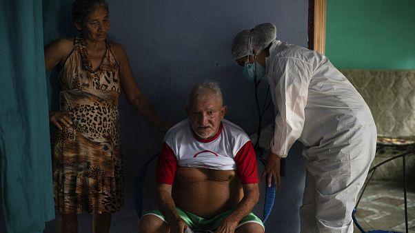 Francisco de Oliveira, 77 anos, respira fundo enquanto é examinado por um médico em Manacapuru, Amazonas
