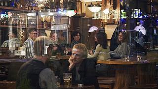 People sit in a bar in Stockholm, Sweden, Wednesday, March 25, 2020. (AP Photo/David Keyton, File)