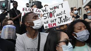 Protesters hold posters during a demonstration Tuesday, June 2, 2020.
