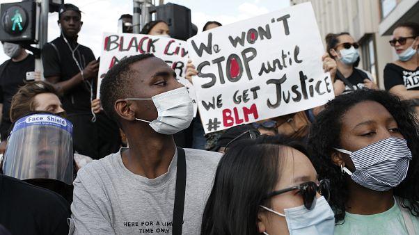 Los manifestantes sostienen carteles durante una manifestación el martes 2 de junio de 2020.