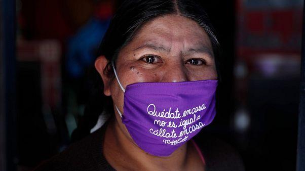 """Una donna boliviana con una mascherina che recita in spagnolo: """"Resta a casa. Non è la stessa cosa di 'stai zitto a casa' """"."""