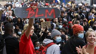 A protester holds up a skateboard with the Black Lives Matter initials in London, Wednesday, June 3, 2020 during a demonstration over the death of George Floyd.