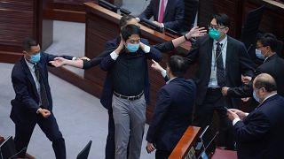 Hui Chi-fung, diputado del bloque prodemocracia, es advertido por la seguridad en la cámara principal del Consejo Legislativo en Hong Kong, el jueves 4 de junio de 2020.