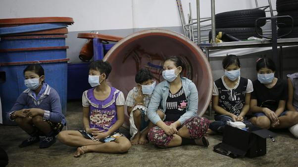 Children and teenagers sit together to be registered by officials during a raid on a shrimp shed in Samut Sakhon, Thailand, on Nov. 9, 2015