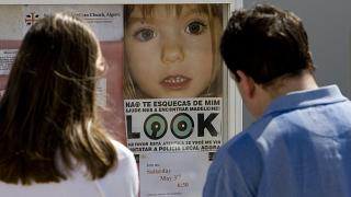 People look at a photograph of British missing girl Madeleine McCann on Friday May 2, 2008 at Praia da Luz beach, Lagos, Portugal