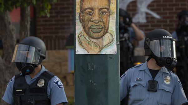 شرطة مينيسوتا تقف أمام عمود رسم عليه صورة لجورج فلويد