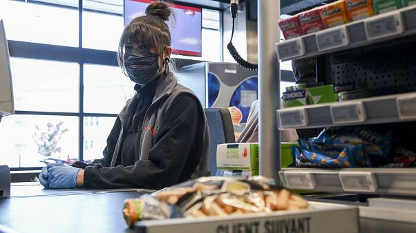 A supermarket employee working with a face mask and gloves during the coronavirus pandemic in Brussels, Belgium