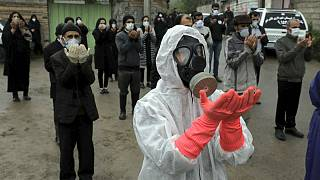 Mourners wearing protective clothing, face masks and gloves, city of Babol, in north of Iran
