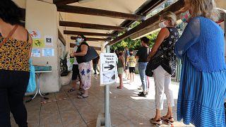 Des Français font la queue devant un tabac de l'autre côté de la frontière italienne le 3 juin