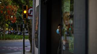 Sunday, May 31, 2020 photo, a waiter wearing a face mask waits for customers in a terrace bar in Barcelona.
