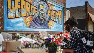 Malaysia Hammond, 19, places flowers at a memorial mural for George Floyd at the corner of Chicago Avenue and 38th Street, Sunday, May 31, 2020.