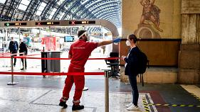 A passenger's temperature is checked at Milan's Central Station, Italy