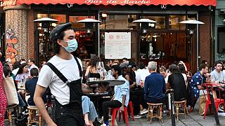 "A waiter wearing a face mask serves clients while people eat and have drinks on the terrace of the cafe-restaurant ""Le Bar du Marche"" in Paris on June 2, 2020"