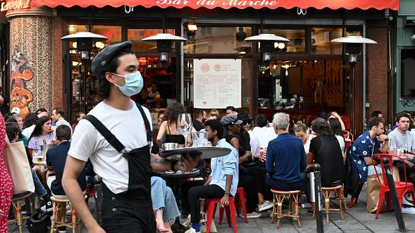 """A waiter wearing a face mask serves clients while people eat and have drinks on the terrace of the cafe-restaurant """"Le Bar du Marche"""" in Paris on June 2, 2020"""
