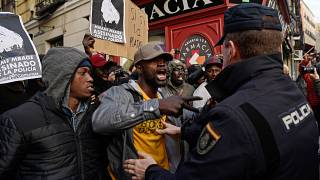 Protesters argue with police officers in Madrid's district of Lavapies on March 16, 2018 during a rally in memory of Senegalese street vendor Mame Mbaye
