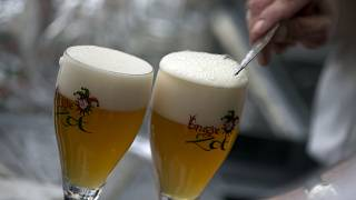 A worker scrapes the foam off of a glass of beer before serving, in Bruges, Belgium.