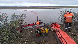 Rescuers work to prevent the spread of an oil spill outside Norilsk