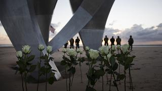 Men in a vintage US WWII uniforms stand behind flowers left at Les Braves monument after a D-Day 76th anniversary ceremony in Saint Laurent sur Mer, Normandy, France, Saturday