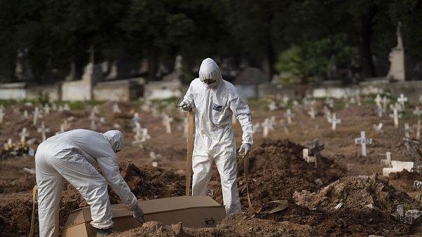 Brezilya'da koronavirüsten ölenlerin mezarcılık işlerini yapan iki görevli.