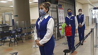 Sosyal mesafe kuralına uyan havaalanı çalışanları.