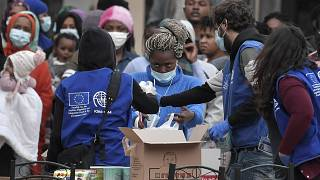 Migrants queue to get sanitisers and other items distributed by the International Organization for Migration (IOM) outside a hotel near Kranidi, Greece, on April 21, 2020