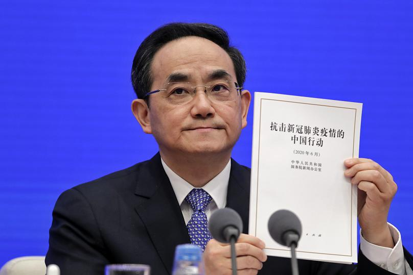 Xu Lin, Vice head of the Publicity Department of Communist Party shows a copy of the white paper on fighting COVID-19 China in action during a press conference at the State Council Information Office in Beijing, Sunday, June 7, 2020