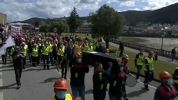 Trabajadores de Alcoa llevando el ataúd que simboliza su muerte laboral