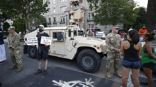 Demonstrators talk to National Guard soldiers as they protest Saturday, June 6, 2020, near the White House in Washington, over the death of George Floyd.