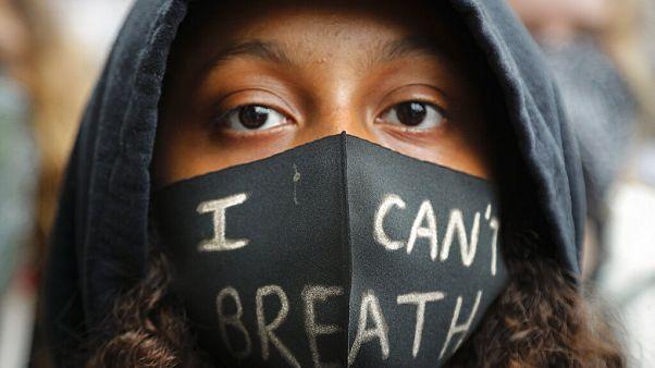 """George Floyd protestolarında maskesinin üzerinde  """"I can't breath"""" (nefes alamıyorum) mesajı taşıyan siyahi bir çocuk."""