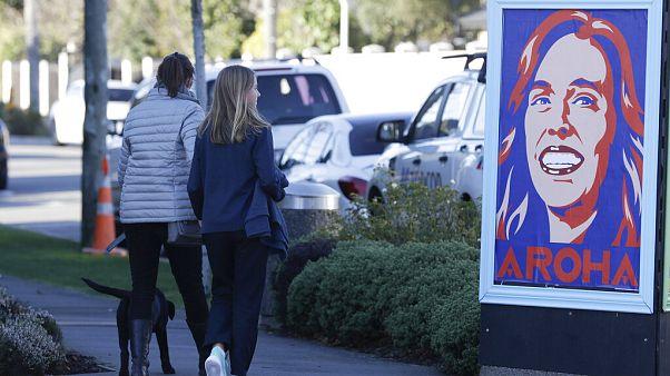 Gente pasa ante un cartel de la primera ministra, Jacinda Ardern