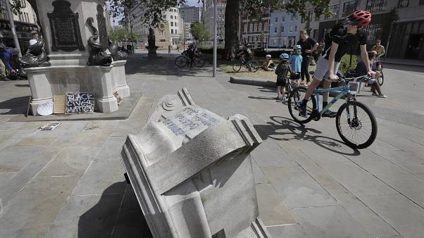 People look at the pedestal of the toppled statue of Edward Colston in Bristol, England, Monday, June 8, 2020.